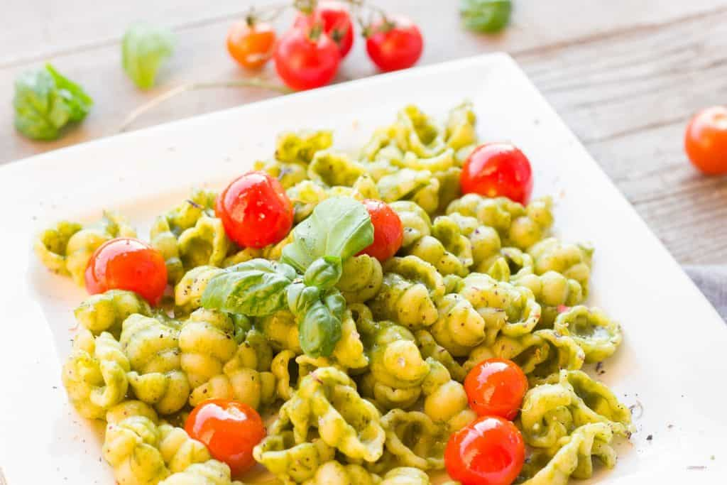 Pasta with pesto sauce basil and tomatoes on it.