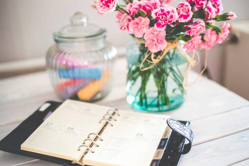 Calendar on a desk with flowers beside it