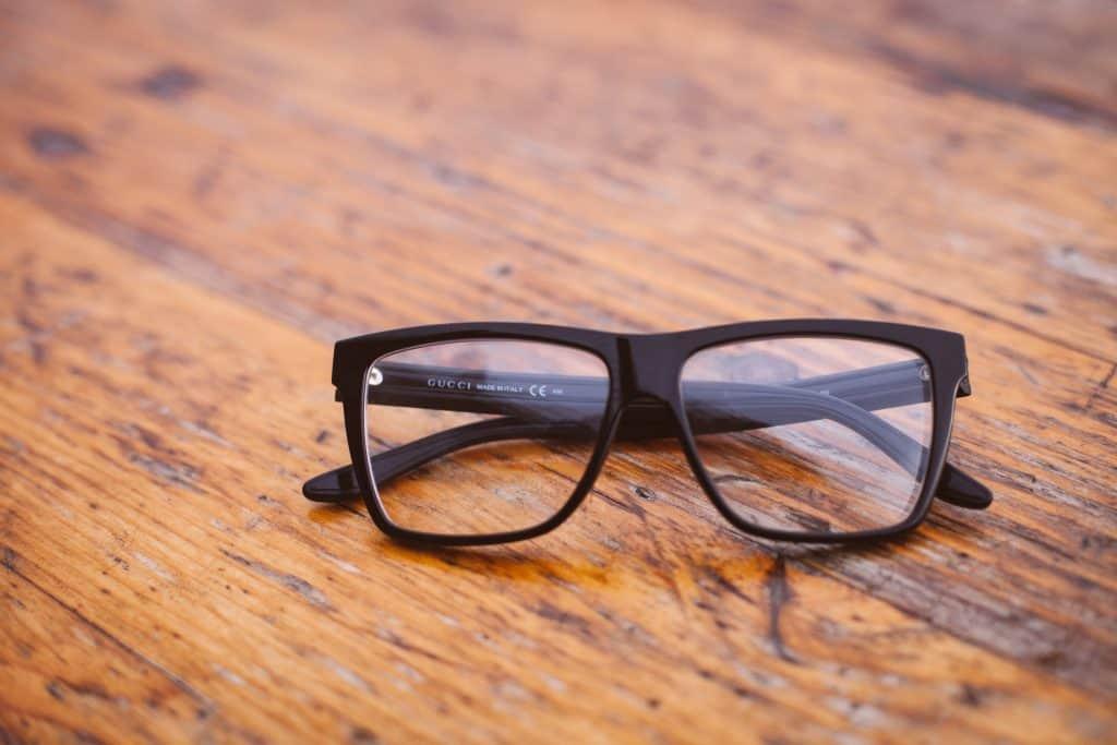 Blacked framed glasses sitting on a wooden desktop