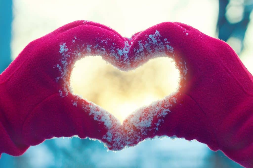 hands in red gloves with snow on them making a heart