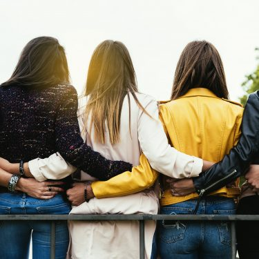 Women linking arms behind their backs