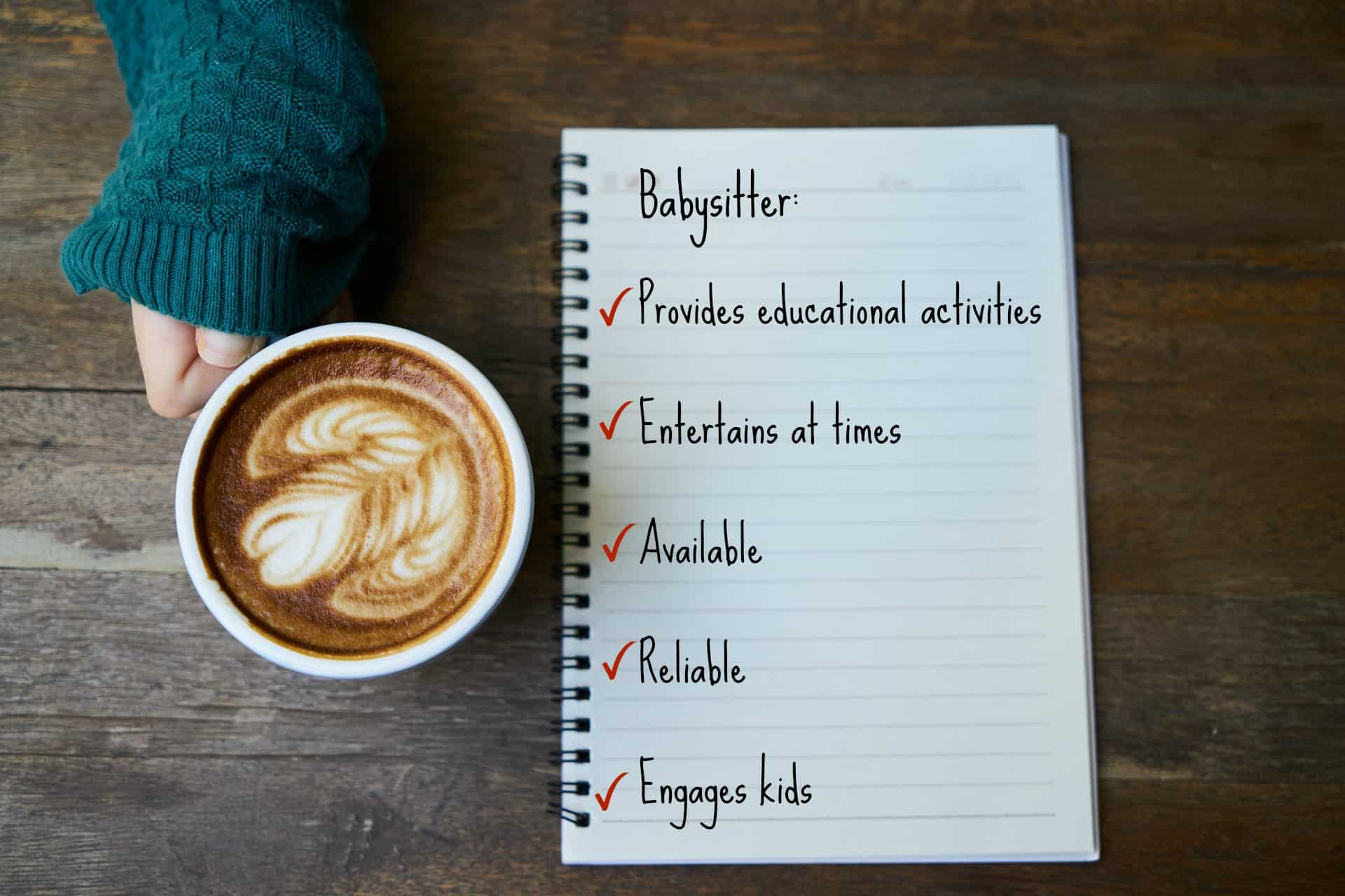 sweater sleeve covering hand holding a latte next to a notebook with Text = Babysitter, Provides educational activities, entertains at times, available, reliable, engages kids.
