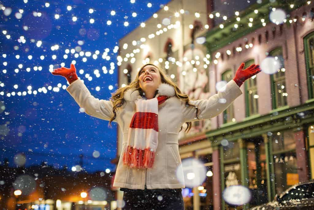 woman looking up at snow under christmas lights