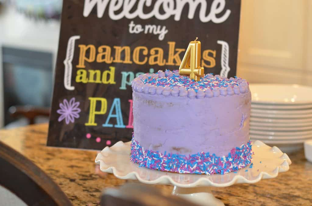 Purple birthday cake with a gold number four candle and birthday sign in the background