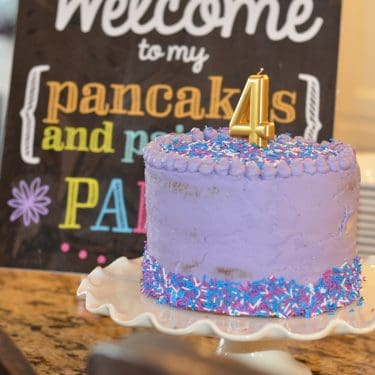 purple birthday cake with sprinkles and gold number four candle