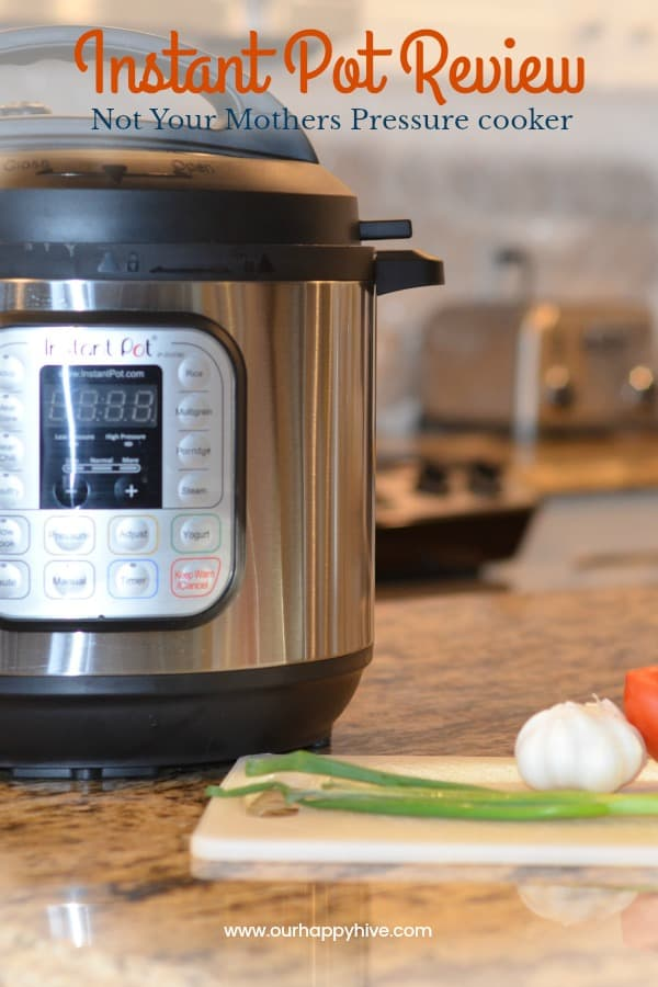 Close up of an Instant Pot sitting on a kitchen counter with a cutting board and vegetables in front and Text Instant Pot Review.