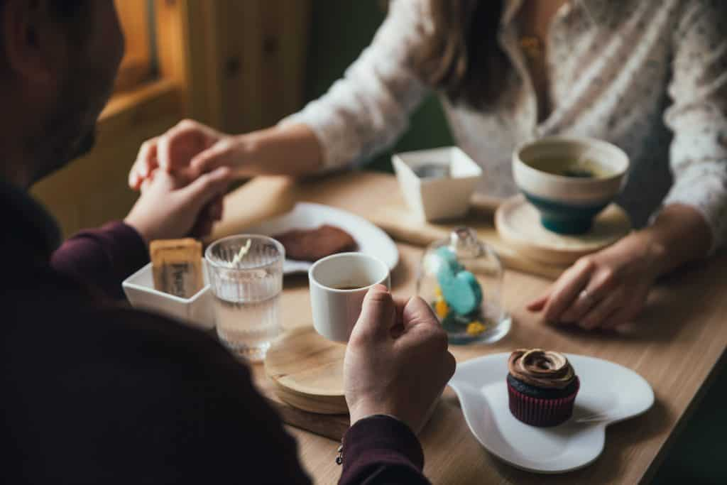 Couple holding hands having coffee and dessert.