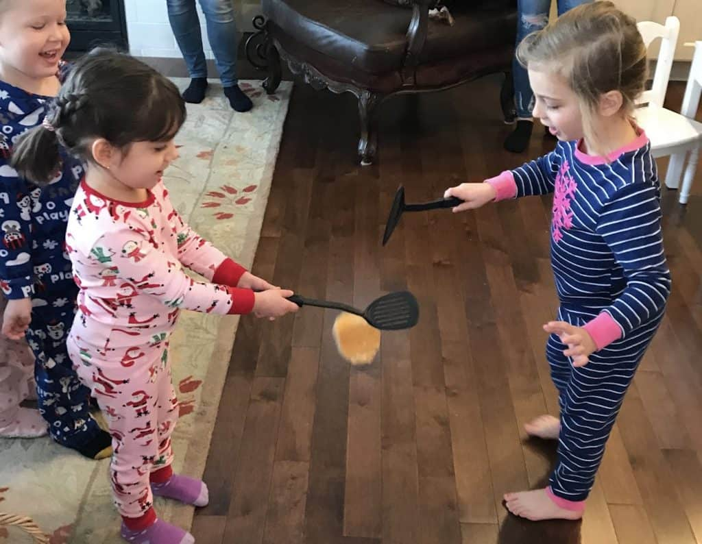 Pancake flipping contest with two preschool girls