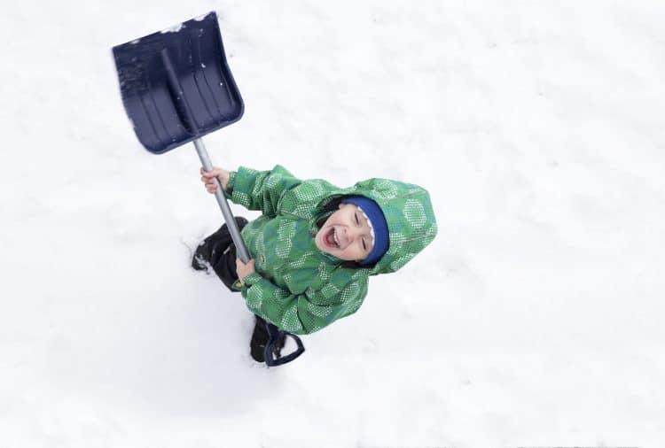 Young boy enthusiastically shoveling snow.