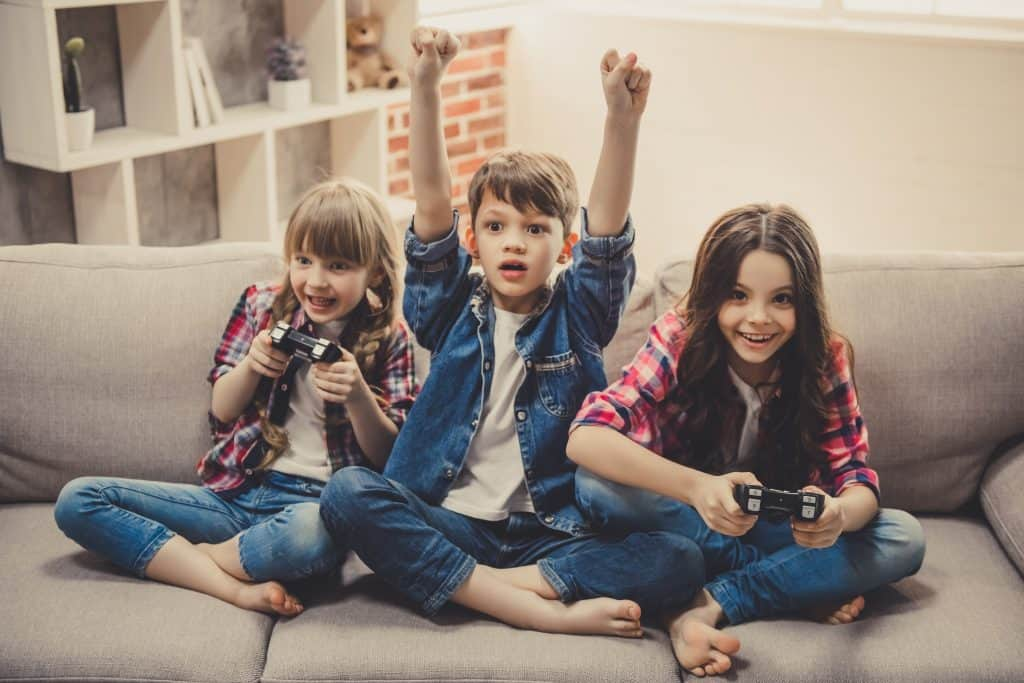 Young kids on a couch playing video games