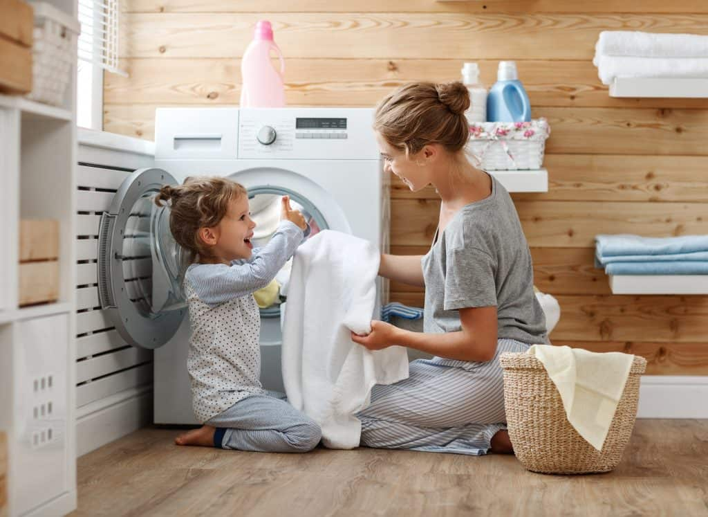 Mom and preschooler daughter doing chores by taking clothes out of the dryer.