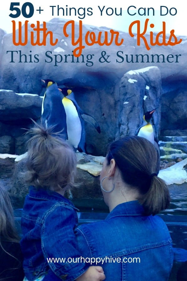 Mom holding toddle while looking at pinguins at the zoo with Text - 50+ Things You Can Do With Your Kids This Spring & Summer