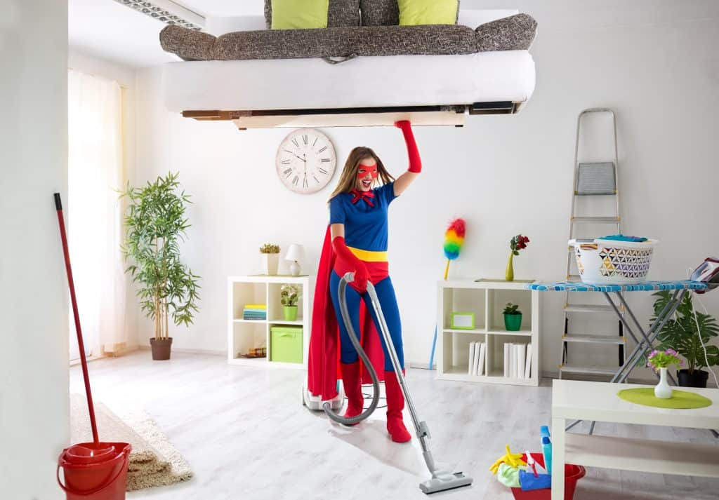 Woman dressed in super-man like outfit holding a couch above her head while vacuuming