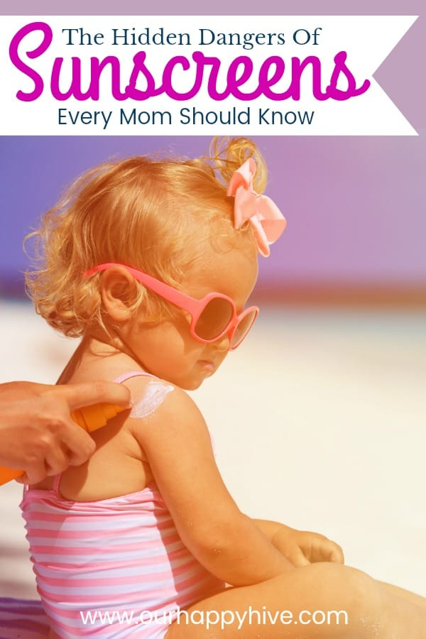toddler girl with pink bathing suit sitting on the beach while mom sprays sunscreen on her with Text - The Hidden Dangers Of Sunscreens Every Mom Should Know