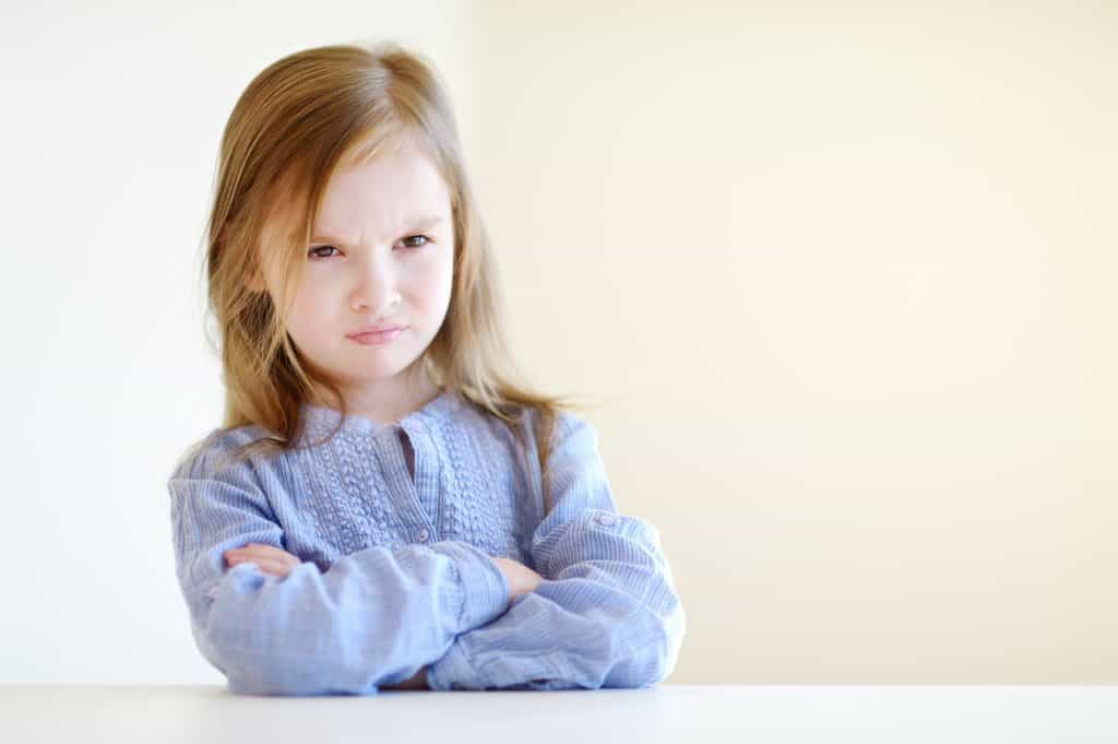 Upset preschool girl withher arms crossed and frowning