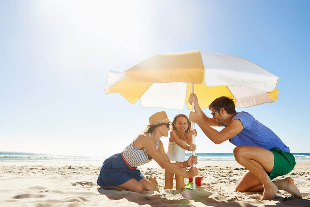 Family of 3 setting up an umbrella on the beach to shade them from the son.