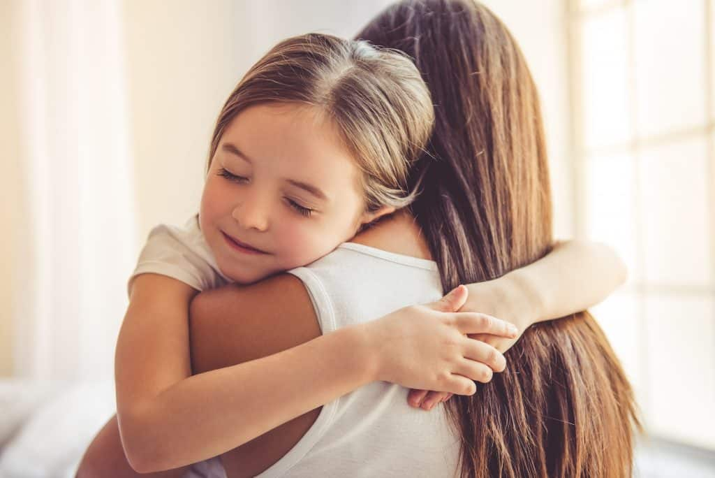 Content girl with her arms around her moms neck hugging her with her eyes closed.