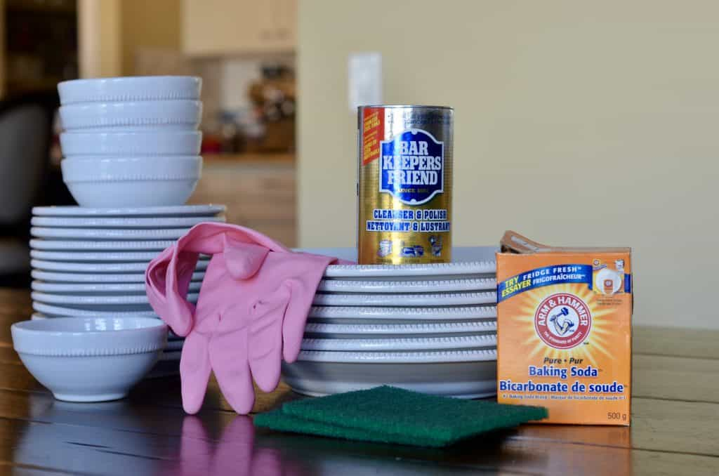 Stack of dishes with Bar Keepers Friend cleaner and Baking Soda, pink kitchen gloves, and green scrub pads.