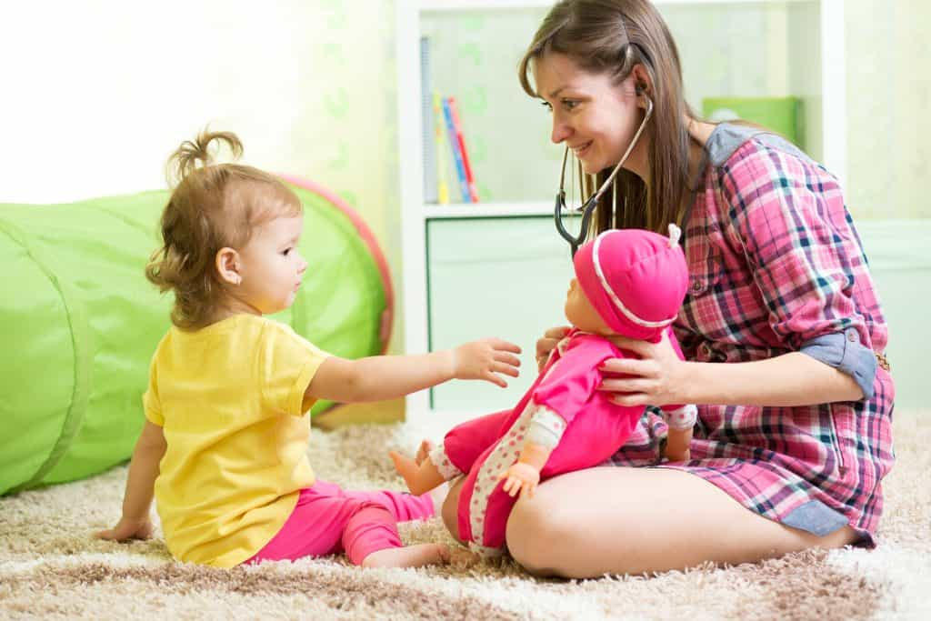 Babysitter playing with a doll with a toddler girl.