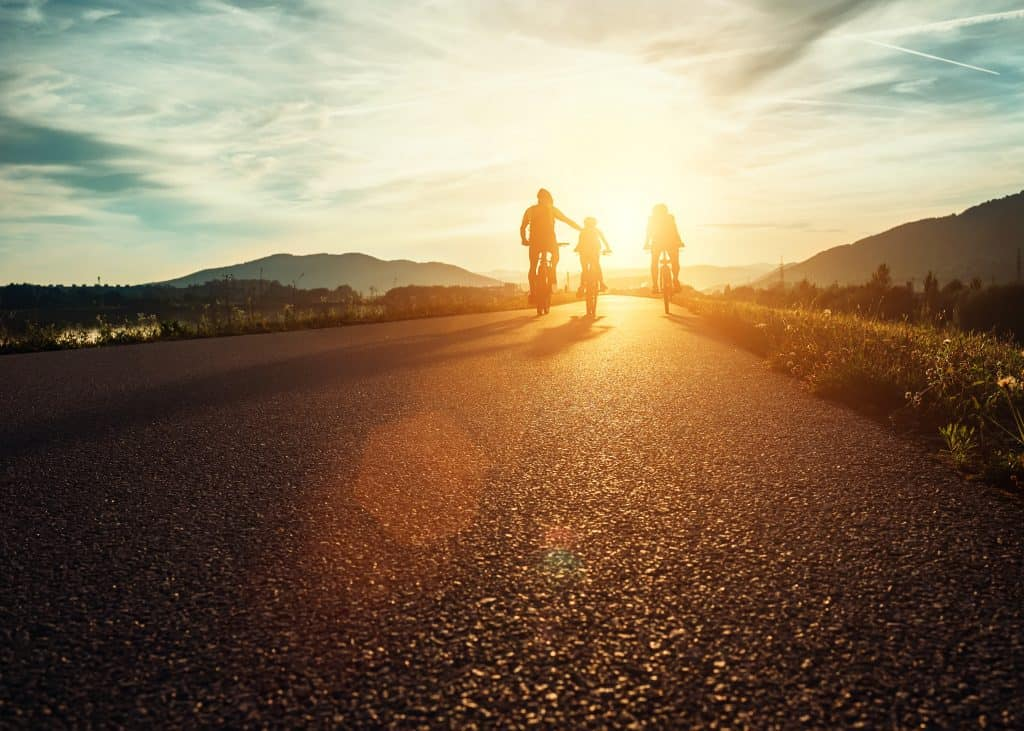 Family of three riding bikes into the sunset.