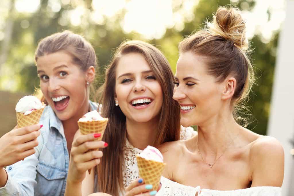 Three pretty ladies having fun eating icecream in a cone.