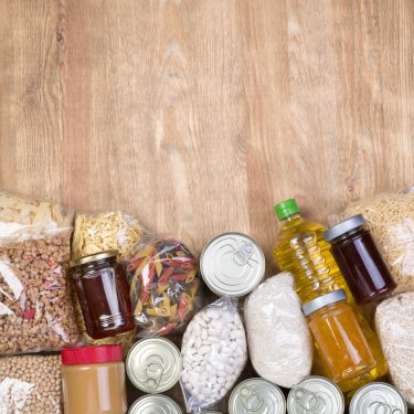 Pantry Food samples on wooden background, top view with copy space