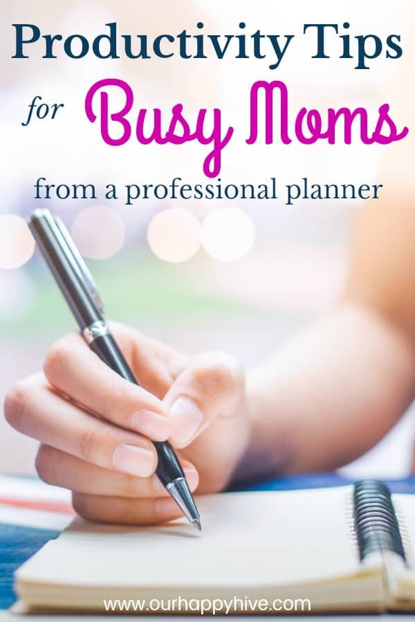 Woman's hand writing on a notebook with a pen on a wooden desk.Background blur backlight with Text Productivity Tips for Bussy Moms from a professional planner