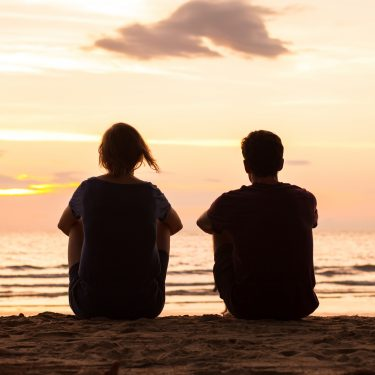 husband and wife sitting on a beach at sunset with their back to you