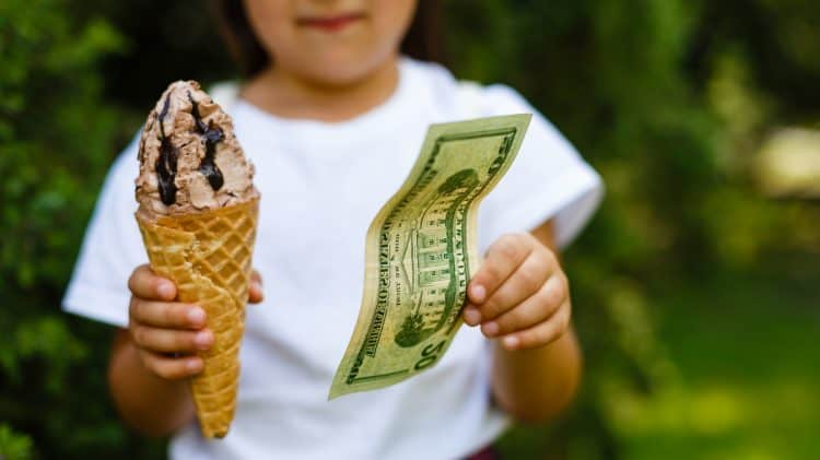 Little girl exchanging ice cream for dollar