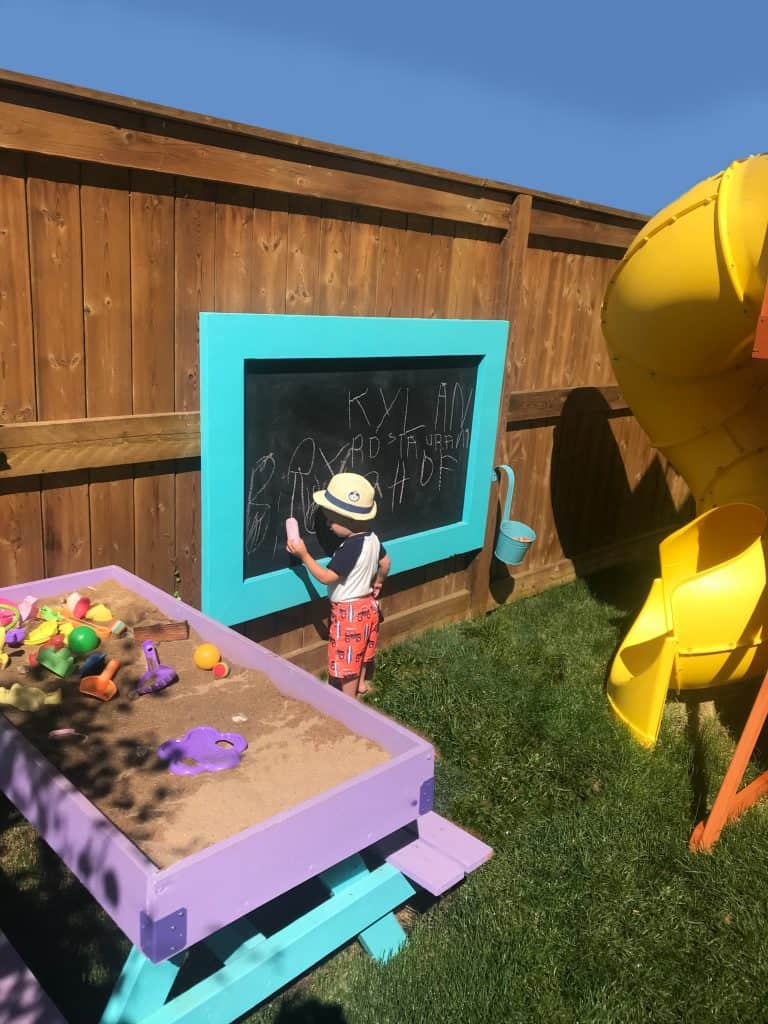 DIY Sand TAble and DIY Outdoor Chalkboard with little boy drawing on it.