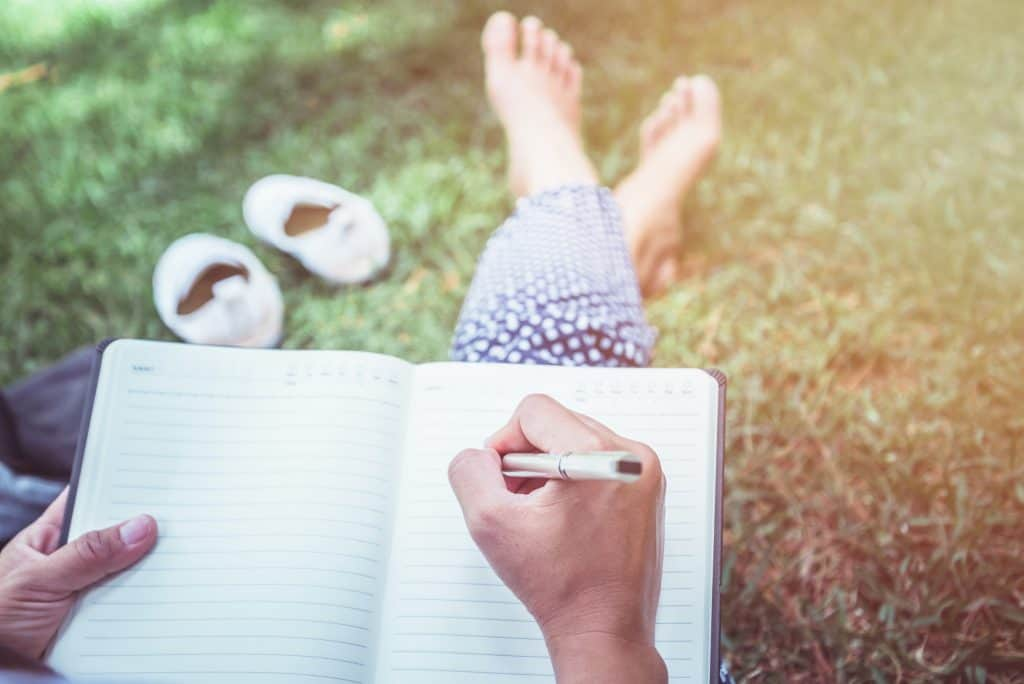 Women reflecting, writing in a journal, outside.