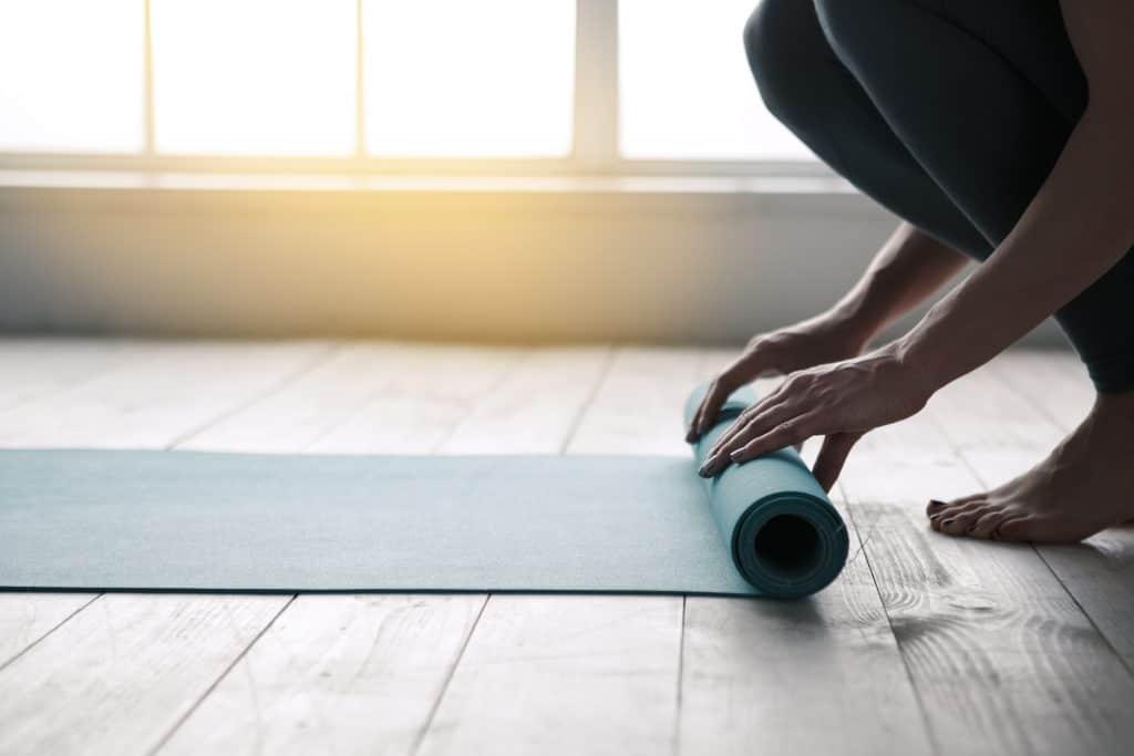 Mom doing yoga rolling mat indoors near window