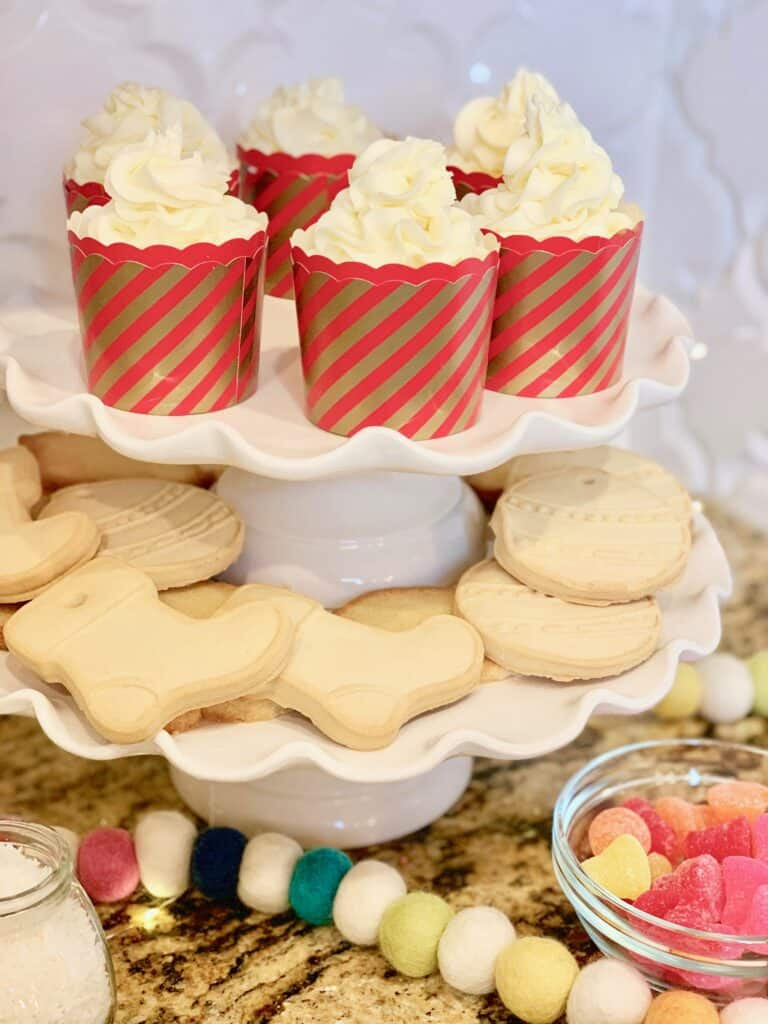 Tiered cookie tray with cupcakes and sugar cookies for holiday party guests to decorate