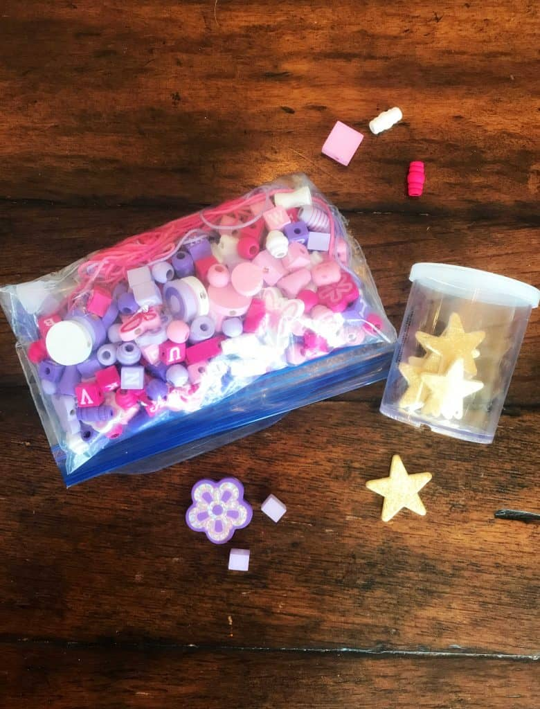 plastic bag with craft supplies including beads and jar with stars
