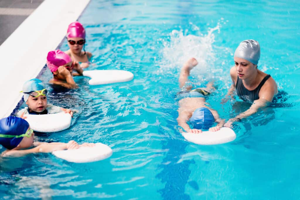 Children in swimming class, practicing with kicking boards, doing rotations, instructor helping one of them. great idea for a clutter free christmas gift.