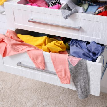 Cluttered chest of drawers with clothes hanging out of it
