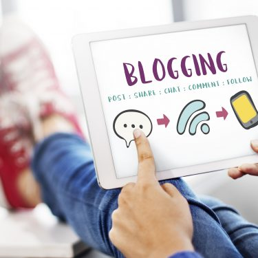 """person holding a tablet with the word """"blogging"""""""