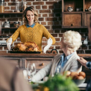a lady getting the turkey out of the oven while family waiting for thanksgiving dinner