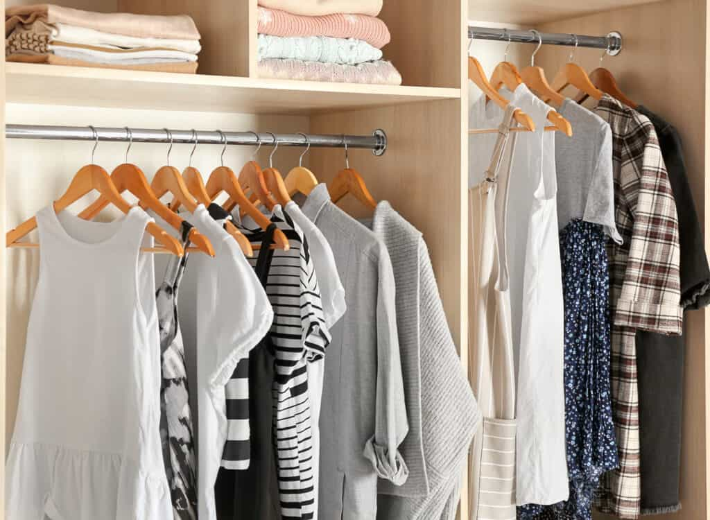 Decluterwomen's clothes hanging in an organized closet after she finished her decluttering project.
