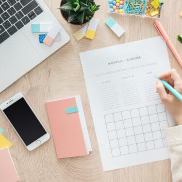 a desktop with a smartphone, a planner, and a woman's hand writing on a planner sheet