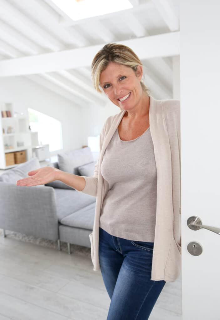 Woman welcoming people to come inside her home after she got started decluttering.