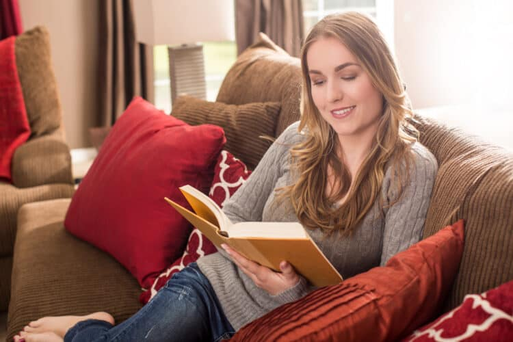Woman sitting on the couch reading home organization and decluttering books