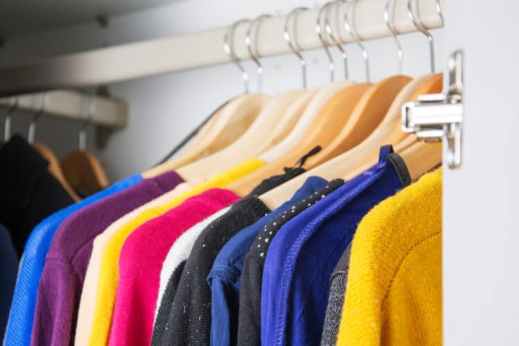 decluttered closet with sweaters neatly hanging up