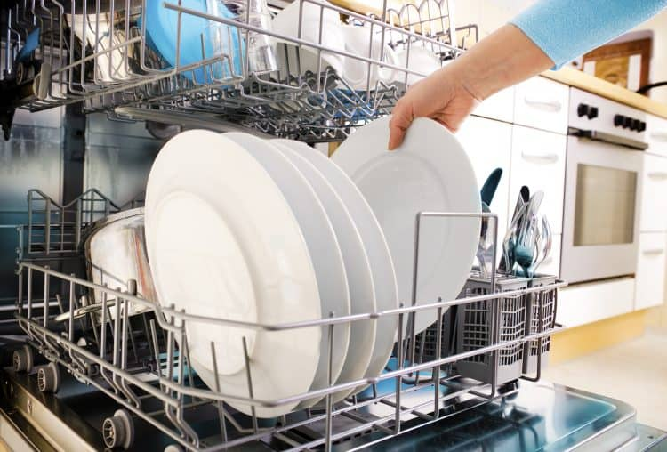 womans hand taking dishes out of the dishwasher while working on keeping her house clean