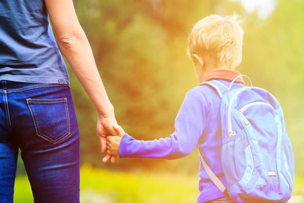 Mom holding child's hand taking him to the first day of school