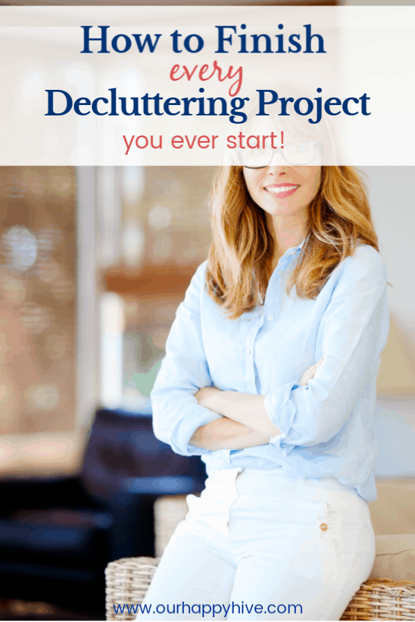 A smiling woman that is happy she finally finished her decluttering project