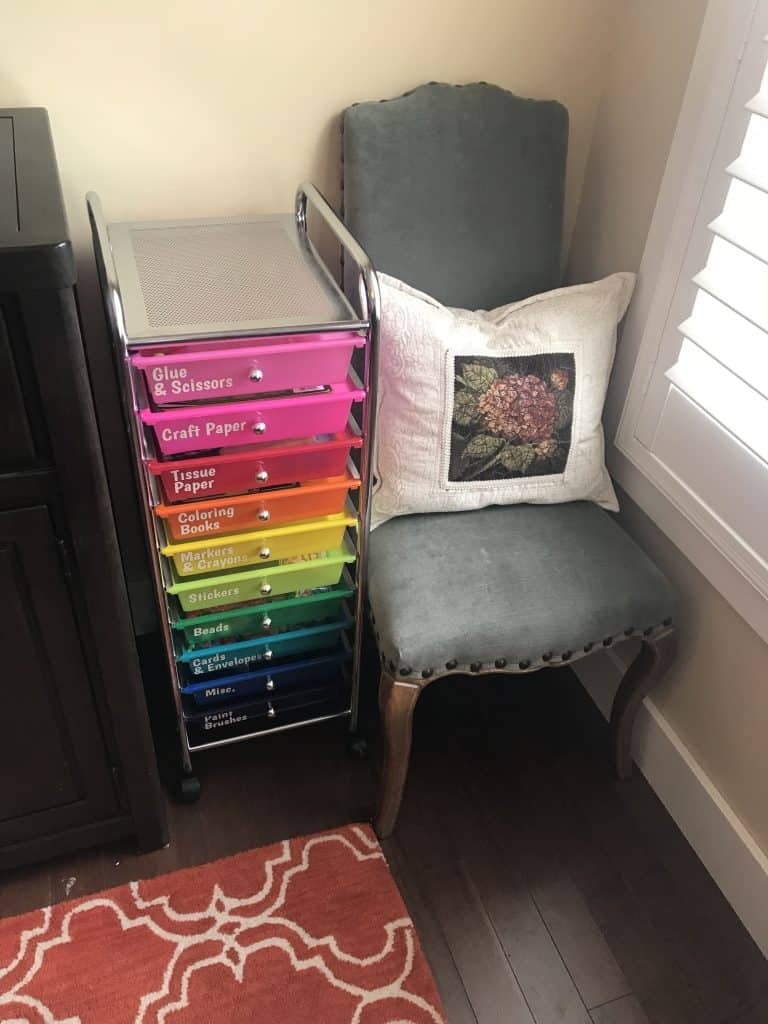 Vertical rainbow colored craft organizing cart with labels on each drawer nested in between a cabinet and a chair.