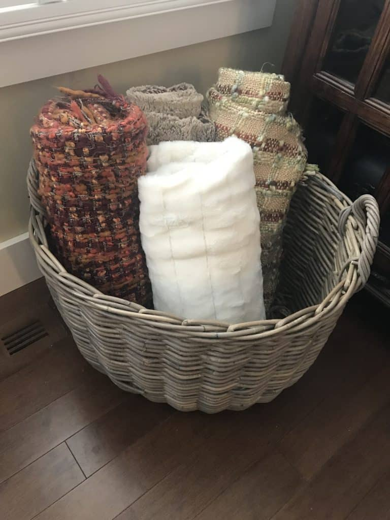 blankets neatly rolled and placed in a basket.