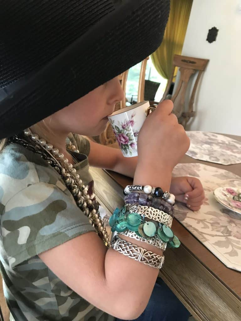 Preschooler dressed up in a broad brimmed hat with lots of jewelry on while sipping tea.