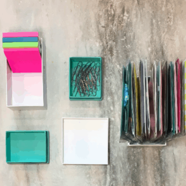 colorful boxes filled with desk supplies and organized standing vertically with the box